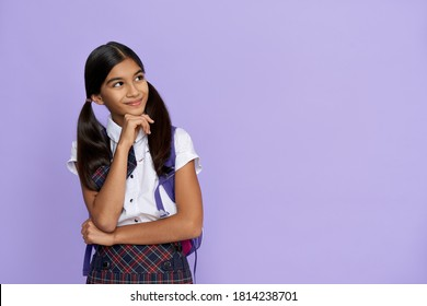 Dreamy smiling indian preteen girl, latin kid schoolgirl wears uniform and backpack looking away at copy space, dreaming, thinking, choosing, advertising standing isolated on lilac violet background.