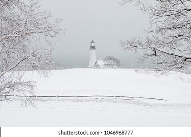 A dreamy snow covered landscape in Maine with a lighthouse in the distance.