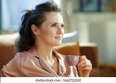 dreamy stylish 40 years old woman in pajamas in the modern house in sunny winter day drinking coffee.