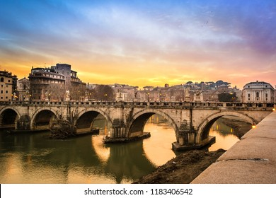 Dreamy sunset in Rome under a cloudy sky, with Tiber river reflecting St. Angelo bridge