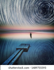 Dreamy surreal landscape with man standing in lake water under starry night sky with star trails.