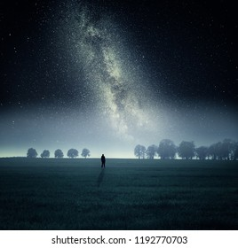 Dreamy surreal landscape with starry night sky and man silhouette.