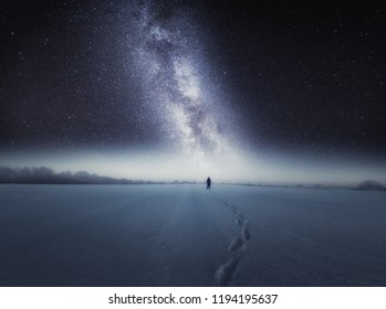 Dreamy surreal landscape with starry night sky and man silhouette standing on snow.