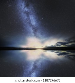 Dreamy surreal landscape with starry sky reflected in water.