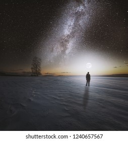 Dreamy surreal winter landscape with starry night sky and man silhouette.