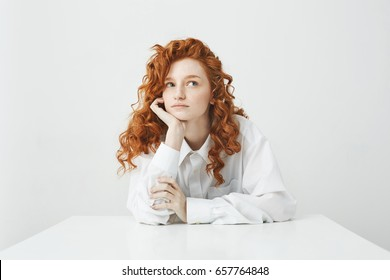 Dreamy tender young girl with red curly hair thinking dreaming sitting at table over white background.