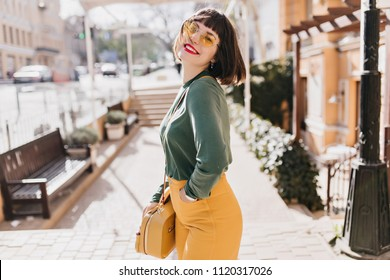 Dreamy white woman with trendy handbag laughing on urban background. Outdoor photo of amazing brunette girl with stylish haircut.