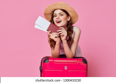 A dreamy woman leaned her hands on a suitcase and holds in her hand a passport with tickets