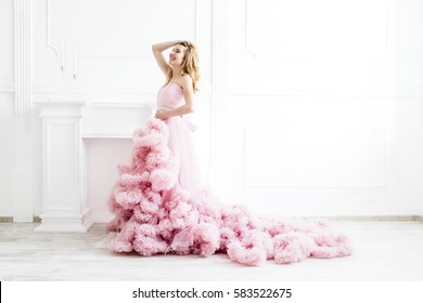 Dreamy woman portrait in a long pale pink ruffled gown in a white modern classic room. Elegant femininity