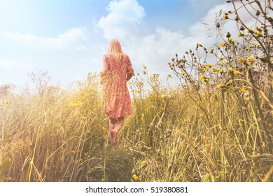 dreamy woman walking in nature towards the sun and the unknown infinite