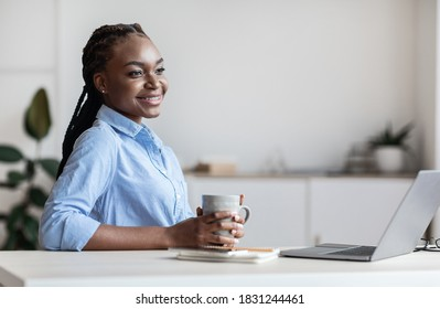 Dreamy Young Black Busines Lady Having Coffee Break At Workplace In Office, Sitting At Desk, African Female Employee Relaxing With Cup Of Hot Drink And Looking Away, Daydreaming At Work, Copy Space