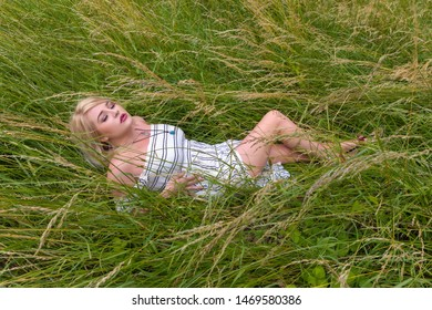 Dreamy young blonde woman relaxing lying down in a meadow with high grasses