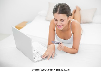 Dreamy young brown haired model in white pajamas shopping online with her laptop in bright bedroom