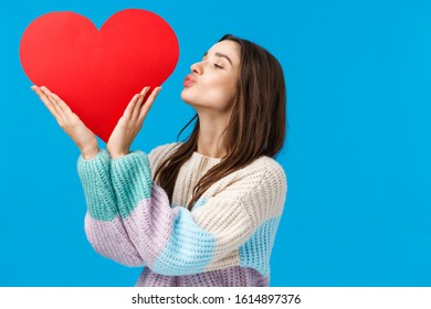 Dreamy young woman cherish her relationship, prepare valentines day gift, kissing big cute red heart sign over left side copy space, standing blue background delighted and upbeat