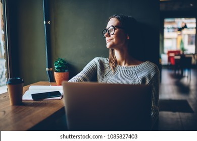 Dreamy young woman freelancer looking out of window and thinking on creative ideas during distance job at modern netbook,Pondering student with laptop computer resting in stylish coworking space
