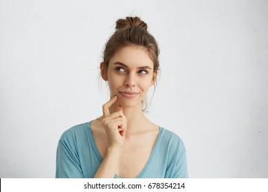 Dreamy young woman looking thoughtfully aside holding her finger on chin dreaming about honey moon with her future husband. Thoughtful female with attractive female having ideas or planning something