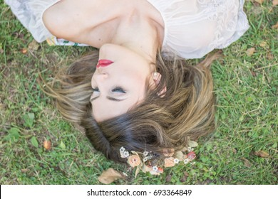Dreamy young woman lying on green grass