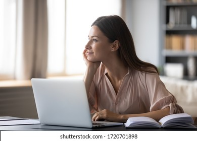 Dreamy young woman pondering ideas, sitting at desk with laptop, distracted from work, beautiful female looking in distance, taking break, dreaming or visualizing at home