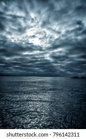 A dreary cloudscape over the ocean diffuses the sunlight as it reflects off the glassy water surface.