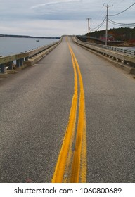 A dreary and gloomy old paved road with yellow striped paint over a bridge along the Maine coast