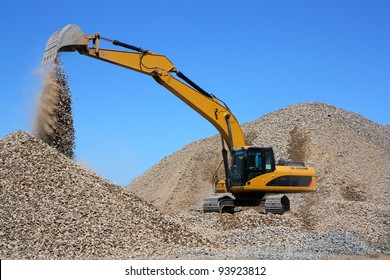Dredge loads a rubble against the blue sky