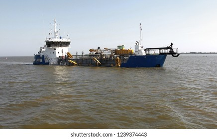Dredger for absorption of trailer bunker during work on land reclamation for new ports. Suction dredge. Dredging in fairway of Dinai River. Cutter suction dredgers when working on land reclamation