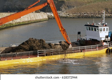 Dredging ship scooping soil from River Esk in Whitby