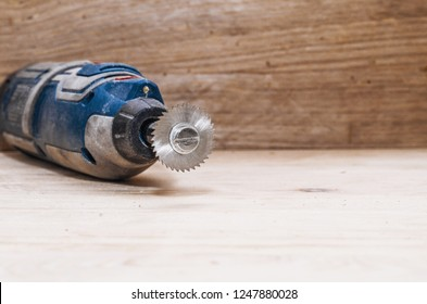 Dremel tool with an installed small circular saw on a wooden board background. Workshop. Manufacture of wooden products. Joiner's cutting tool