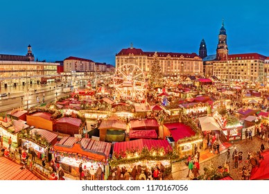 Dresden in Christmas time, Germany. Spectacular view on famous traditional European Christmas market on the central city square, dusk scenery, illuminated stalls and market places, amusement park.
