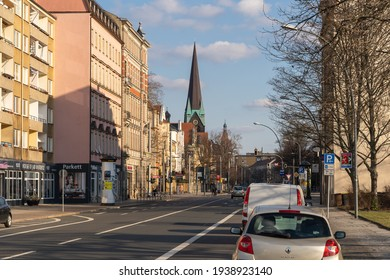 DRESDEN, GERMANY - 17. March 2021: View along a street to Fetscherplatz in Johannstadt on a sunny spring day. Cars are parking next to the street and the church is visible in the urban skyline.