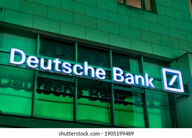 DRESDEN, GERMANY - 29. January 2021: Deutsche Bank logo on a wall illuminated in blue color. Bank branch in Germany. Front facade of a building which is reflecting green light.