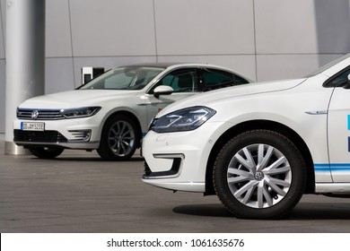 DRESDEN, GERMANY - APRIL 2 2018: Plug-in hybrid Volkswagen Golf GTE and e-Golf electric cars stand by charging station in front of Transparent Factory on April 2, 2018 in Dresden, Germany.