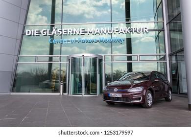 DRESDEN, GERMANY - APRIL 2 2018: Plug-in hybrid Volkswagen e-Golf electric car stands in front of the Glaserne Manufaktur - Transparent Factory on April 2, 2018 in Dresden, Germany.