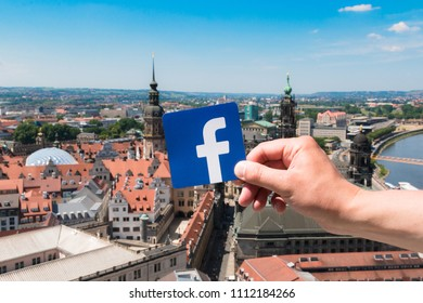 Dresden, Germany. June, 2018. Logo Facebook and the city on the background. Concept. Man holds the logo of a popular company.