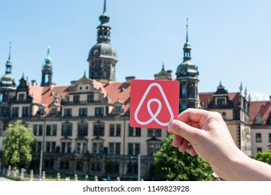 Dresden, Germany. June, 2018. Travel around the world with Airbnb. Logo Airbnb and the city on the background. Home concept. Man holds the logo of a popular company.
