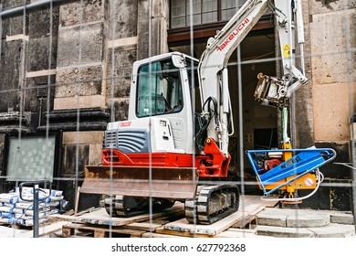 DRESDEN, GERMANY, MARCH 21, 2017: small excavator is working on the church reconstruction on the city street