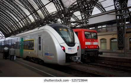 Dresden, Germany - November 27, 2016 - Modern silver suburban train and red electric locomotive in the station Dresden - Hauptbahnhof (main railway station).