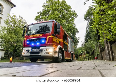 Dresden, Saxony, Germany - 22 June 2017: German emergency fire truck (Feuerwehr Dresden) on the road. Fire service after a storm with uprooted trees in Dresden Striesen.