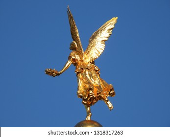 Dresden,Germany-17 February 2019: golden figure of Greek goddess of fame Pheme or Fama with wings and wreath on top of the dome of the main building of Dresden Academy of Fine Arts