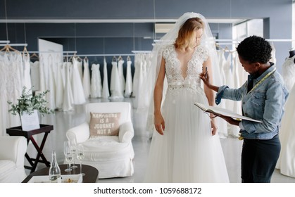 Dress designer fitting bridal gown to woman in boutique. Women checking and making adjustment to wedding gown in professional fashion designer studio.