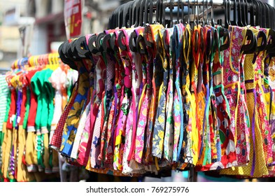 Dress for girl hung in front of retail shop for sale,on hangers in a busy road in Hyderabad,India