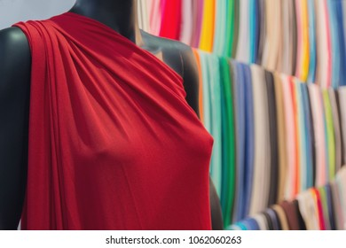 Dress on a mannequin and a choice of multi-colored fabric in a store. Fashion