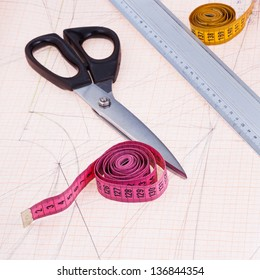 dress pattern at graph paper and tailors shears, ruler, measure tapes