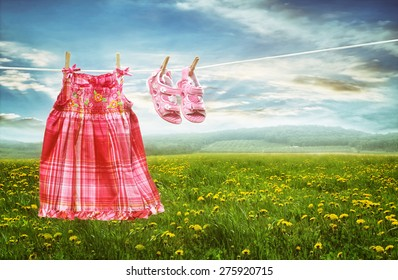 Dress and sandals on clothesline in summer fields of dandelions