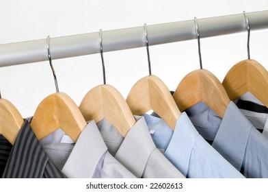 Dress shirts on wooden hangers.