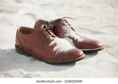 Dress shoes for groom on the beach with blowing sand.
