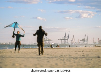 Dressed adults with a kite at the seashore. A port with cranes for cargo ships on background