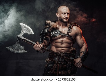 Dressed in antique light armour with fur bald and violent viking with muscular build poses in dark atmospheric background holding two handed double axe