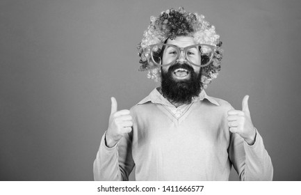 Dressed up for birthday party. Man in fashion wig gesturing thumbs up. Bearded man in clown wig hairstyle. Hipster man wearing rainbow wig hair. Happy man with long beard and curl wig, copy space.