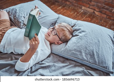 Dressed in casual clothing cheerful and smiley boy reads book lying down on a bed in living room.